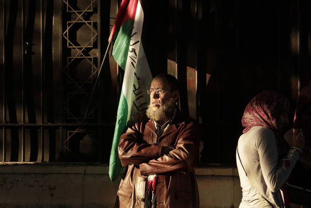 "A Egyptian man stands under a Palestinian flag during a protest in solidarity with Gaza after Israel launched its operation on Wednesday with the assassination of Hamas' top military commander in Cairo, Egypt, Thursday, Nov. 15, 2012. Egypt asked the United States to push Israel to stop its offensive against Hamas militants in the Gaza Strip, warning that the violence could ""escalate out of control,"" the Foreign Ministry said Thursday. (AP Photo/Nariman El-Mofty)"