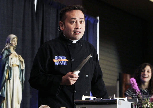 "Rev. Leo Patalinghug speaks at the Oklahoma Catholic Women's Conference at the Clarion Meridian Hotel & Convention Center in Oklahoma City, OK, Saturday, Feb. 18, 2012. He started his ""Grace Before Meals"" movement and is known for his cooking and how he incorporates that into the gospel messages he shares. By Paul Hellstern, The Oklahoman"