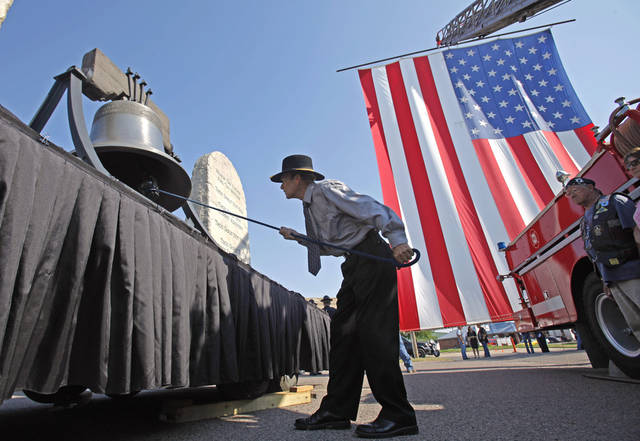 David Hall rings a bell in front of a giant Madill Fire Department flag flown at services for Lt. Joe Lee Cunningham on Saturday, April 27, 2011, in Madill, Okla.  Cunningham died from non-combat-related injuries while serving in Afghanistan on August 13, 2011.  Photo by Steve Sisney, The Oklahoman