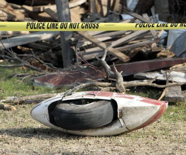 Part of the landing gear from a light plane crash rests under police tape on Saturday, Dec. 10, 2011, in Chickasha, Okla.  Two people died in the crash that occurred overnight one hundred yards south of Grand Ave. and three miles west of the city.  The airplane came down between two abandoned farm buildings. Photo by Steve Sisney, The Oklahoman