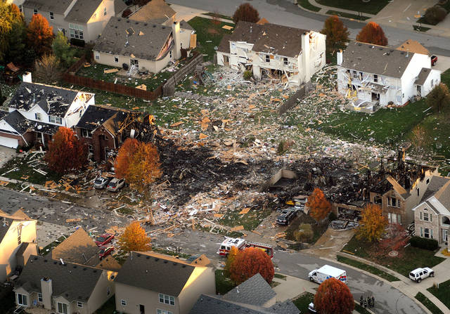 FILE - This aerial file photo from Nov. 11, 2012, shows the two homes that were leveled and the numerous neighboring homes that were damaged from a massive explosion that sparked a huge fire and killed two people in Indianapolis. Authorities launched a homicide investigation Monday, Nov. 19, 2012 into the house explosion that killed a young couple and left numerous homes uninhabitable in an Indianapolis neighborhood. (AP Photo/The Indianapolis Star, Matt Kryger, File) NO SALES