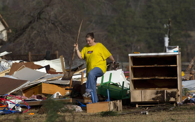 Amber Butler walks through the wreckage of her home in Oak Grove, Ala., Monday, Jan. 23, 2012. Jefferson County sheriff's spokesman Randy Christian said severe storms produced a possible tornado that moved across northern Jefferson County around 3:30 a.m., causing damage in Oak Grove, Graysville, Fultondale, Center Point, Clay and Trussville.  (AP Photo/Dave Martin) ORG XMIT: ALDM108