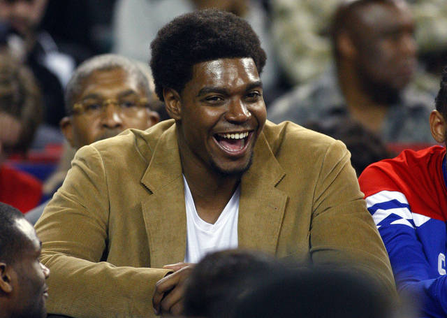 Philadelphia 76ers' Andrew Bynum watches the action from the bench during an NBA preseason basketball game against the Brooklyn Nets in Atlantic City , N.J., Saturday, Oct. 13, 2012. The Nets defeated the 76ers 108-105 in overtime. Bynum is sitting out the preseason to rest his achy knees. (AP Photo/Rich Schultz)