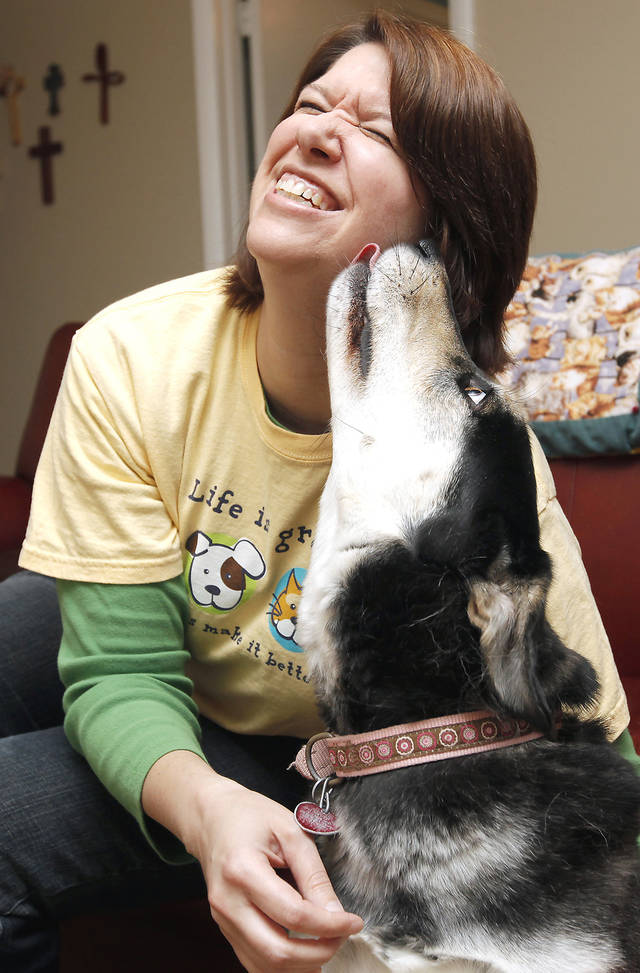 Photographer Melissa Rawlings gets a kiss from her dog, Kyla. Rawlings' photo book of rescued dogs raises money for Paws For Life and Edmond Animal Shelter. PHOTO BY NATE BILLINGS, THE OKLAHOMAN