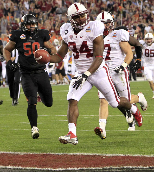 Stanford running back Jeremy Stewart (34) scores a touchdown as Oklahoma State defensive end Jamie Blatnick (50) pursues during the first half of the Fiesta Bowl NCAA college football game Monday, Jan. 2, 2012, in Glendale, Ariz. (AP Photo/Ross D. Franklin) 