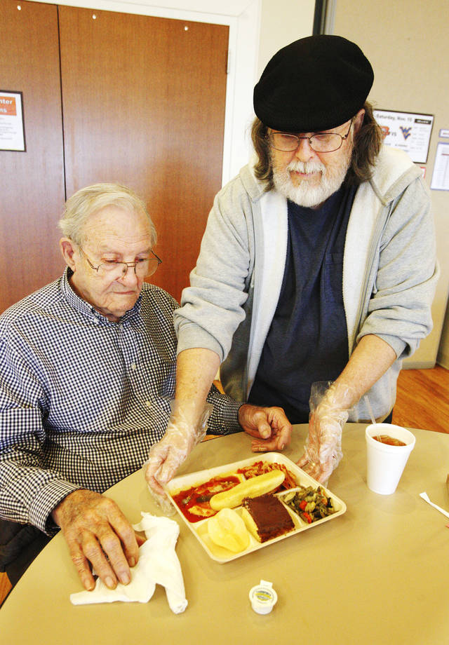 Volunteer Charlie Chodrick, right, serves Don Smith as people 55 and older eat lunch at the Edmond Senior Center in Mitch Park.