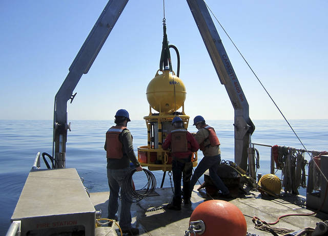 "This April 28, 2013 photo released by Woods Hole Oceanographic Institution shows a robotic device being deployed to detect red tide in the Gulf of Maine. Red tide monitoring is going high-tech with a robotic ""laboratory in a can."" A garbage can-sized canister was deployed in late April in the ocean waters off southern Maine to collect and transmit data about toxin-producing algae blooms, known as red tides, that show up in the Gulf of Maine each spring.(AP Photo/Woods Hole Oceanographic Institution & Northeastern University, Isaac Rosenthal)"
