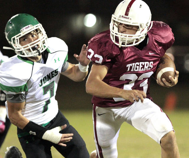 Tuttle's Tanner Brannon (33) turns a corner chased by Jones player Andrew Case (7) in high school football as Tuttle plays Jones on Friday, Oct. 19, 2012 in Tuttle, Okla.  Photo by Steve Sisney, The Oklahoman