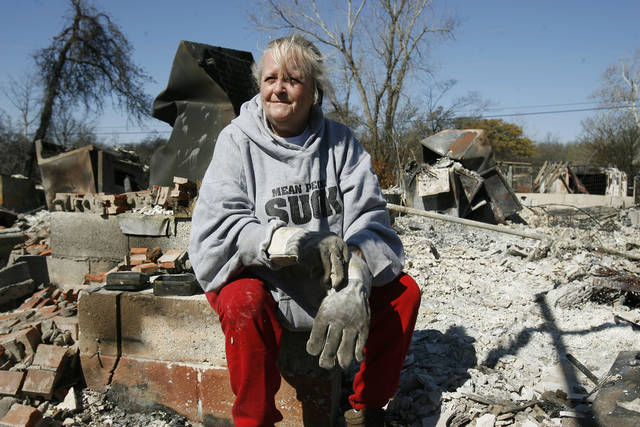 Linda Sadler, sister of the owner of this home which burned at 1001 Pacific Dr. in Choctaw, Oklahoma, sifts through the charred rubble for salvageable items, Saturday, April 11, 2009. Photo by Paul Hellstern, The Oklahoman