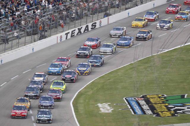 Tony Stewart, front left, and Carl Edwards, front right, lead the pack on the restart following a caution during the NASCAR Sprint Cup Series auto race at Texas Motor Speedway in Fort Worth, Texas, Sunday, Nov. 6, 2011. Stewart went on to win the race. (AP Photo/Mike Fuentes)