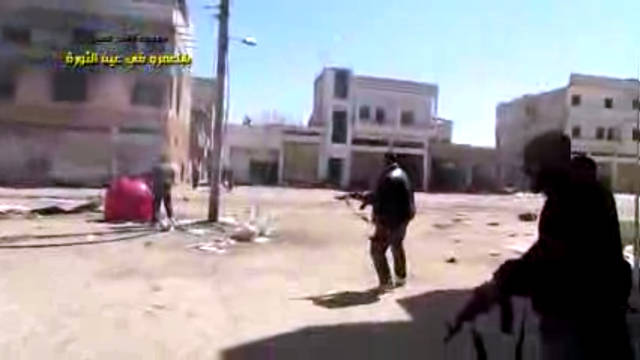 In this image taken from video obtained from the Shaam News Network, which has been authenticated based on its contents and other AP reporting, Syrian rebels battle with regime forces in Homs, Syria, Tuesday, March 26, 2013. Mortars rounds struck several areas of Damascus on Tuesday, killing several people, a government official said, while anti-regime activists said Syrian troops seized control of a neighborhood in the central city of Homs that is considered a symbol of opposition to President Bashar Assad's regime. (AP Photo/Shaam News Network via AP video)