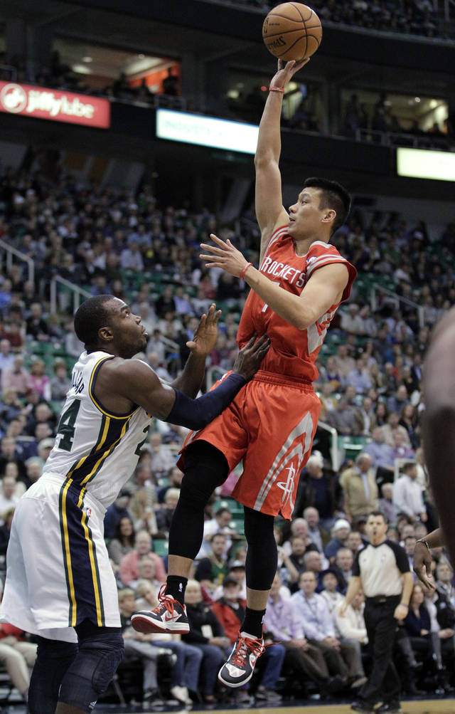 Houston Rockets guard Jeremy Lin, right, lays the ball up as Utah Jazz forward Paul Millsap (24) defends in the first quarter during an NBA basketball game Monday. Nov. 19, 2012, in Salt Lake City. (AP Photo/Rick Bowmer)