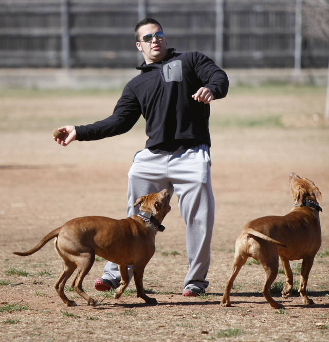 Juan Lopez tosses a tennis ball for his dogs, Lexus and Copper, at the Edmond dog park.  Photo By Paul Hellstern, The Oklahoman archives