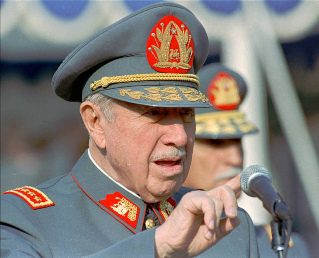 FILE - In this Aug. 22, 1997 file photo Chilean Army Commander in Chief Gen. Augusto Pinochet tests the microphone during a military ceremony in Santiago, Chile. Former Liberian President Charles Taylor is part of a long parade of leaders guilty or accused of similar, and in some cases far more appalling, crimes in modern history. Here is what happened to some: Gen. Augusto Pinochet: the former Chilean president, died in 2006 at age 91 in a military hospital, putting an end to a decade of intensifying efforts to bring him to trial for human rights abuses blamed on his regime. He had terrorized his opponents for 17 years after taking power in a bloody coup. (AP Photo/Santiago Llanquin, file)