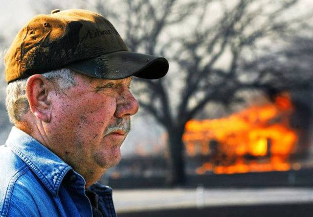 FIRES / WILDFIRES: Homeowner Tom Simon stands in front of his home at 19850 NE 23 as a house next door to him is burning to the ground.  Simon, wearing a blackened ball cap and his face dark with soot,  worked with other neighbors using garden hoses to spare their homes from being claimed by the flames of raging wildfires in Harrah Friday afternoon, March 11, 2011. Authorities had asked Simon to leave his property as flames neared, but he refused, choosing to stay and do what he could to protect his home. Photo by Jim Beckel, The Oklahoman ORG XMIT: KOD