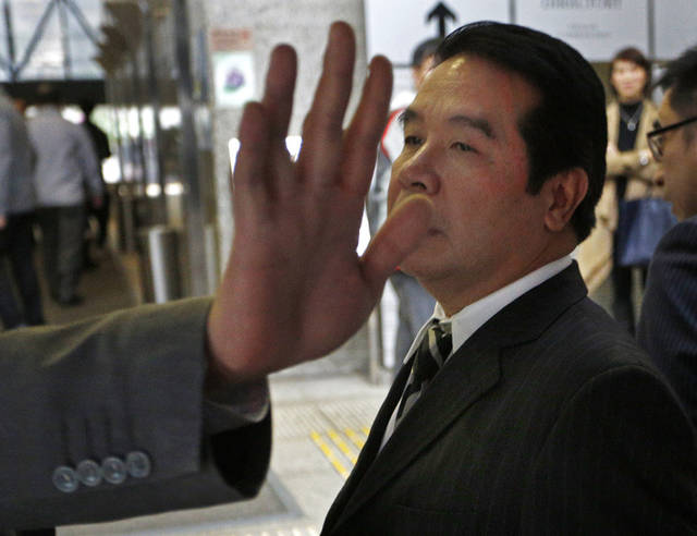 FILE - In this Nov. 28, 2012 file photo, Birmingham City owner Carson Yeung, right, leaves the court while a bodyguard tries to block photographers's cameras in Hong Kong.   Birmingham City owner Yeung's lawyer applied for the money laundering case against the wealthy Hong Kong businessman to be thrown out Monday, April 29, 2013,  the latest wrinkle in a drawn-out legal battle.(AP Photo/Vincent Yu, File)
