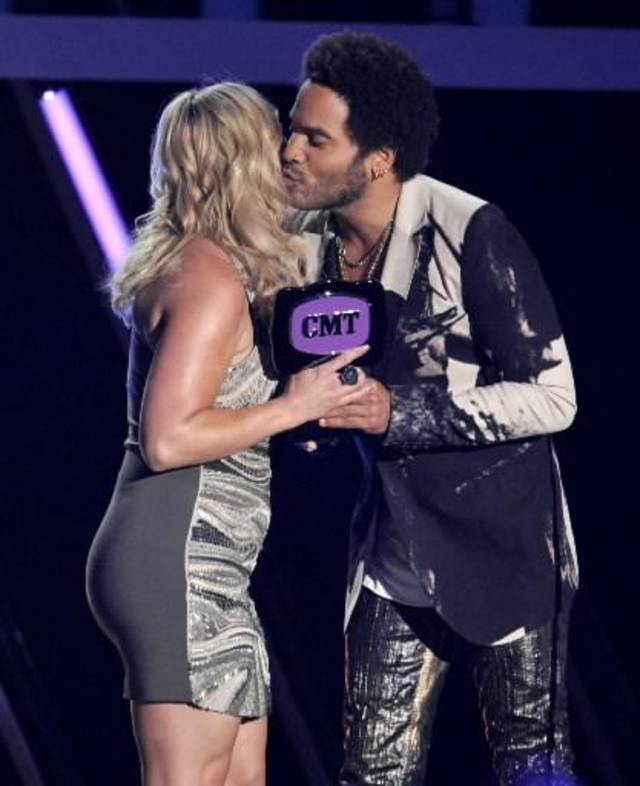 Lenny Kravitz kisses Tishomingo resident Miranda Lambert while presenting her with the female video of the year trophy at Wednesday's CMT Music Awards. (AP)