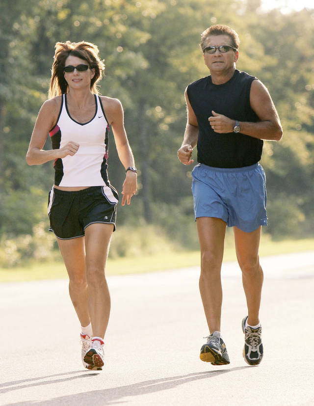 Wayne and Tina King jog along the street at their home in Edmond, Okla., Monday, August 21, 2006. Dr. King and his wife Tina, who works in his office, are avid, rabid marathoners and they  travel in a large motorhome to compete in dozens of marathons a year. Photo by Paul Hellstern / The Oklahoman.