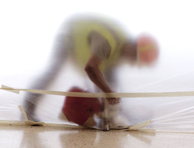 A construction worker sands a parquet floor surrounded by plastic sheeting in the soon to be completed food court at the Devon Energy Center in Oklahoma City, OK, Friday, Feb. 24, 2012. By Paul Hellstern, The Oklahoman