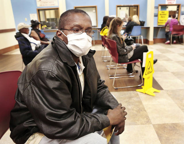 Walter Harris, of Oklahoma City, wears a protective mask while sitting with other clients in the waiting room Thursday at the Oklahoma City-County Health Department. Harris came for a flu shot and said he wore the mask to reduce the risk of catching germs while he was in the waiting area. PHOTO BY JIM BECKEL, THE OKLAHOMAN