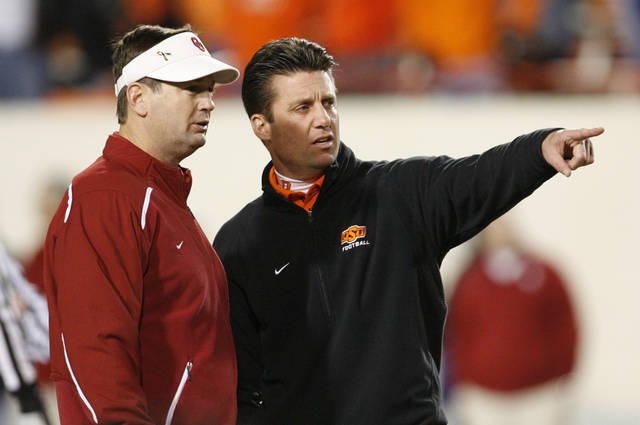 OU head coach Bob Stoops, left, and OSU head coach Mike Gundy talk before the college football game between the University of Oklahoma Sooners (OU) and Oklahoma State University Cowboys (OSU) at Boone Pickens Stadium on Saturday, Nov. 29, 2008, in Stillwater, Okla. STAFF PHOTO BY NATE BILLINGS
