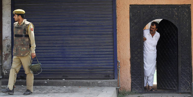 An Indian policeman stands guard as a Kashmiri watches from a doorway during a curfew imposed in the area in Srinagar, India, Tuesday, June 26, 2012. A fire destroyed a revered Muslim shrine in Indian-administered Kashmir on Monday, prompting anti-government protests by residents angered over an alleged slow response by firefighters. (AP Photo/Mukhtar Khan)