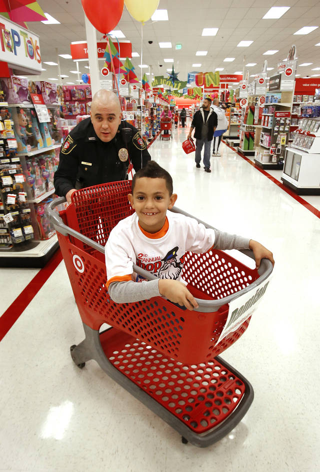 Moore Police officer Aaron Smith helps Damian Johnson, 7, shop at Target during the Second Annual Shop with a Cop on Saturday, Dec. 8, 2012 in Moore, Okla.  Photo by Steve Sisney, The Oklahoman