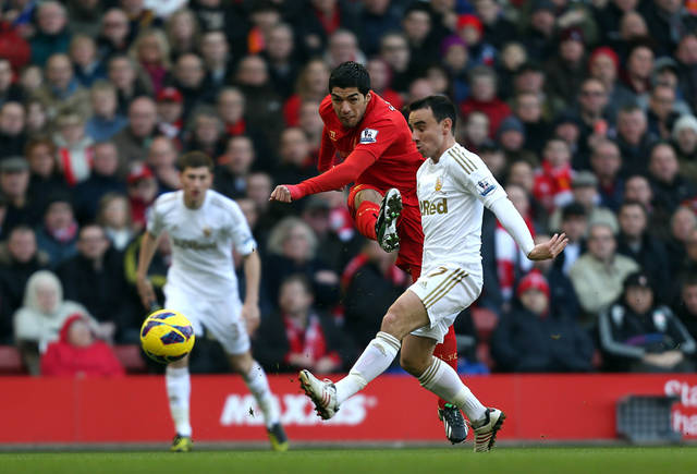 Swansea City's Leon Britton, centre right, attempts to block a shot by Liverpool's Luis Suarez, centre,  during the Barclays Premier League match at Anfield, Liverpool, Sunday Feb. 17, 2013. (AP Photo/ David Davies, PA)  UNITED KINGDOM OUT