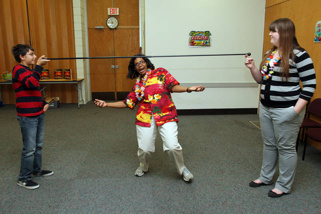 Warr Acres Library staff member Cheryl Coleman demonstrates how to do the limbo Thursday night as Omar Samara and Maegyn Doyle hold the stick during a Hawaiian luau at the library. The event was one of many special activities the Warr Acres Library offers for students. Other upcoming events include the LEGO Club at 2:30 p.m. Jan. 21 and an origami class for teens at 2 p.m. Jan. 28. PHOTOS BY HUGH SCOTT, FOR THE OKLAHOMAN