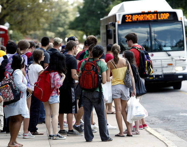 University of Oklahoma students wait at a campus bus stop after attending classes. Cleveland Area Rapid Transport employees reported that OU students are taking advantage of public transportation this week to travel between classes and their housing units. OU students began the fall semester of classes Monday.  PHOTO BY STEVE SISNEY, THE OKLAHOMAN