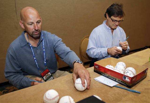 Colorado Rockies manager Walt Weiss, left, and Los Angeles Dodgers manager Don Mattingly, right, autograph baseballs at baseball's winter meetings on Tuesday, Dec. 4, 2012, in Nashville, Tenn. (AP Photo/Mark Humphrey)