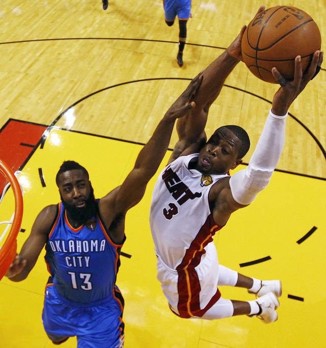 Miami Heat shooting guard Dwyane Wade (3) dunks over Oklahoma City Thunder guard James Harden (13) during the second half at Game 3 of the NBA Finals basketball series, Sunday, June 17, 2012, in Miami. The Heat won 91-85. (AP Photo/Mike Ehrmann, Pool)