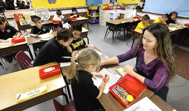 Kindergarten teacher Tammy Whitaker works with students at Santa Fe South Elementary School in  Oklahoma City. Photo by PAUL B. SOUTHERLAND, the oklahoman