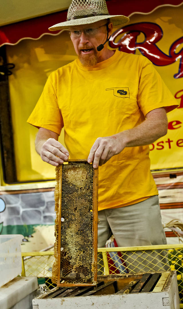 Rick Schantz demonstrates how to remove honey from a bee hive at the Oklahoma State Fair at State Fair Park on Friday, Sept. 14, 2012, in Oklahoma City, Oklahoma.  Photo by Chris Landsberger, The Oklahoman
