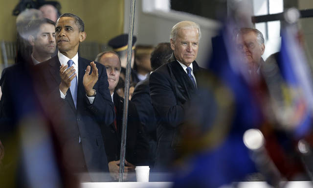 President Barack Obama and Vice President Joe Biden watch the Inaugural parade walk down Pennsylvania Avenue en route to the White House, Monday, Jan. 21, 2013, in Washington. Thousands  marched during the 57th Presidential Inauguration parade after the ceremonial swearing-in of President Barack Obama. (AP Photo/Steve Helber) ORG XMIT: DCMS181