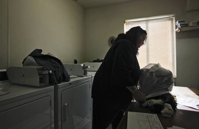 Jill Thompson works in the laundry room as she sorts, washes and folds residents laundry at the City Rescue Mission on Thursday, Nov. 17, 2011. in Oklahoma City, Okla. Thompson has battled physical and substance abuse that played major role in leading to her being homeless and residing in the shelter. Photo by Chris Landsberger, The Oklahoman