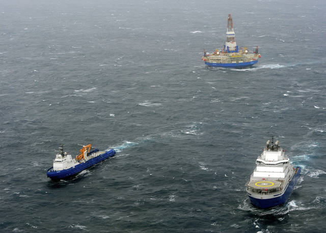 In this photo provided by the United States Coast Guard, the tugs Aiviq and Nanuq tow the mobile drilling unit Kulluk while a Coast Guard helicopter from Air Station Kodiak transports crew members on Saturday, Dec. 29, 2012, 80 miles southwest of Kodiak City, Alaska. The tug lost the initial tow Thursday and suffered several engine failures prompting the deployment of response assets by the Coast Guard and Royal Dutch Shell. (AP Photo/United States Coast Guard, Petty Officer 1st Class Sara Francis)