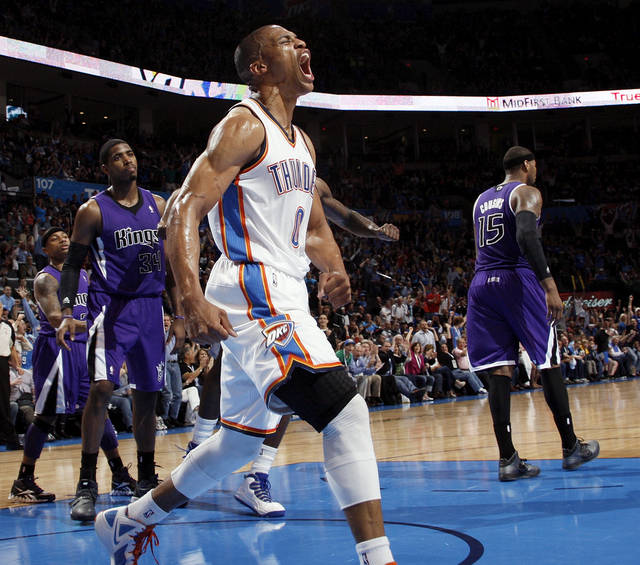 Oklahoma City's Russell Westbrook (0) reacts in front of Sacramento's Isaiah Thomas (22), Jason Thompson (34) and DeMarcus Cousins (15) after dunking the ball on a lob pass from Kevin Durant during the NBA basketball game between the Oklahoma City Thunder and the Sacramento Kings at Chesapeake Energy Arena in Oklahoma City, Friday, April 13, 2012. Photo by Nate Billings, The Oklahoman