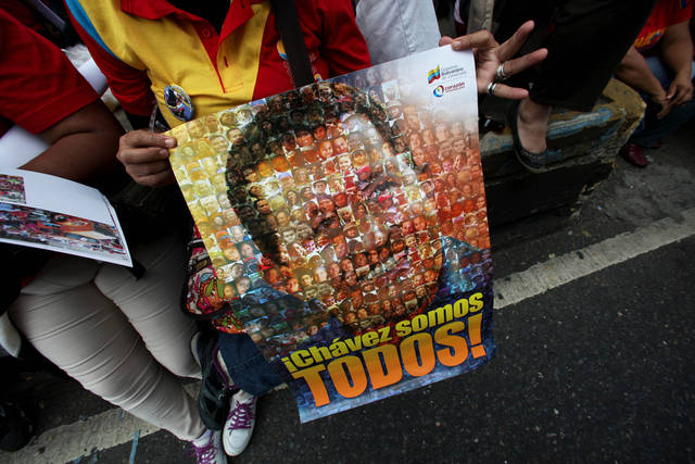 "A supporter of Venezuela's President  Hugo Chavez holds poster of him with the slogan in Spanish ""We are all Chavez!"" at rally by Chavez supporters in Caracas, Venezuela, Wednesday, Jan. 23, 2013. The cult of personality that Chavez long nurtured has been flourishing like never before as he confronts an increasingly difficult struggle against the mysterious cancer that afflicts him. (AP Photo/Fernando Llano)"