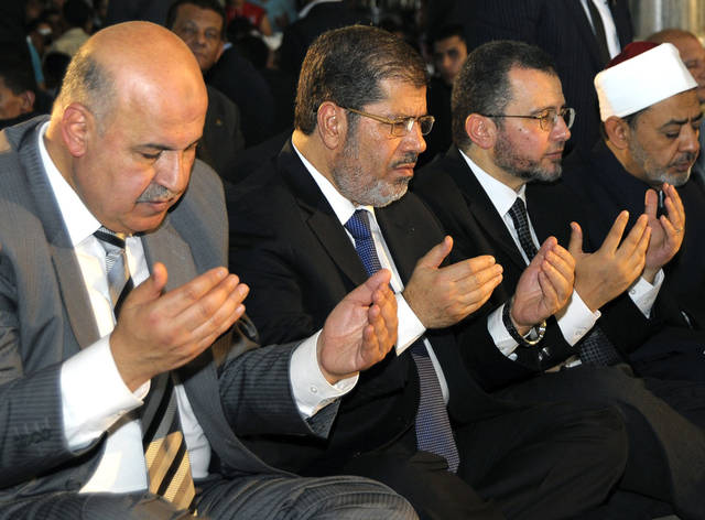 FILE - In this Sunday, Aug. 19, 2012 file photo released by the Egyptian Presidency, Egyptian Vice President, Mahmoud Mekki, left, President Mohammed Morsi, second left, Prime Minister Hesham Kandil, third left, and the Grand Sheik of Al-Azhar, Ahmed el-Tayeb, right, attend Eid el Fitr prayers in Amr Ibn Al-As mosque to mark the start of a three-day Muslim holiday that marks the end of the Muslim holy month of Ramadan. Egypt's state TV says Vice President Mahmoud Mekki has resigned. Mekki's Saturday, Dec. 22, 2012 resignation was announced with more than five hours to go of voting in the second and final phase of a referendum on a disputed, Islamist-backed constitution.  (AP Photo/Egyptian Presidency, File)