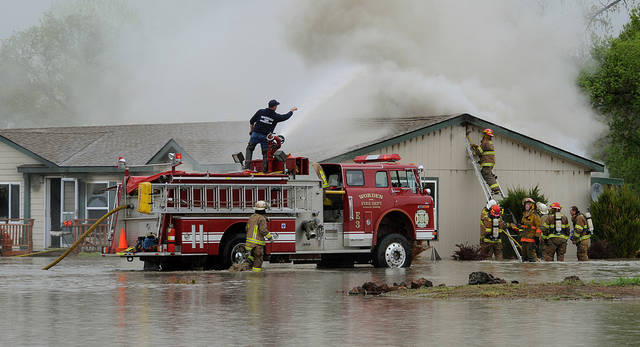 The Worden Volunteer Fire Department battles a fire in a home in the flooded area along Pryor Creek in Huntley, Mont., Sunday, May 22, 2011. Pryor Creet is flooding the Pryor Creek Golf Course and homes along the creek in Huntley. (AP Photo/Billings Gazette, Larry Mayer)