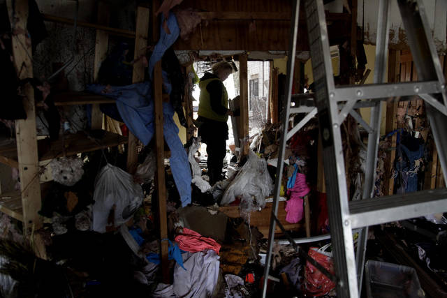 Marina Sverdlov tries to clean out her flood ravaged home in Staten Island, New York, Friday, Nov. 2, 2012. Sverdlov and her family are currently living with her mother in a one-bedroom apartment so they are trying to find an affordable rental as quickly as possible.Sandy, the storm that made landfall Monday, caused multiple fatalities, halted mass transit and cut power to more than 6 million homes and businesses.  (AP Photo/Seth Wenig) ORG XMIT: NYSW129