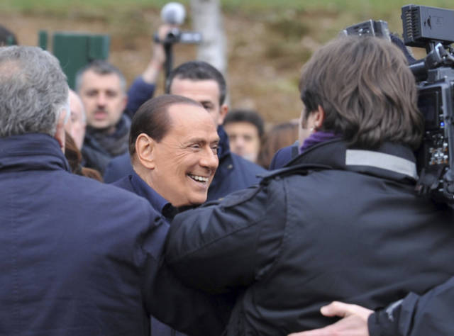 "In this photo provided by AC Milan press office, billionaire media baron Silvio Berlusconi is surrounded by media as announces he is running for a fourth term as premier,  during a visit to the AC Milan Milanello soccer training center, near Milan, Italy, Saturday, Dec. 8, 2012. ""I'm running to win,"" Berlusconi told reporters outside the training facilities of his soccer team AC Milan. Berlusconi resigned in disgrace a year ago and it seems he is poised to re-enter politics.  (AP Photo/Gianni Buzzi, AC Milan press office)"