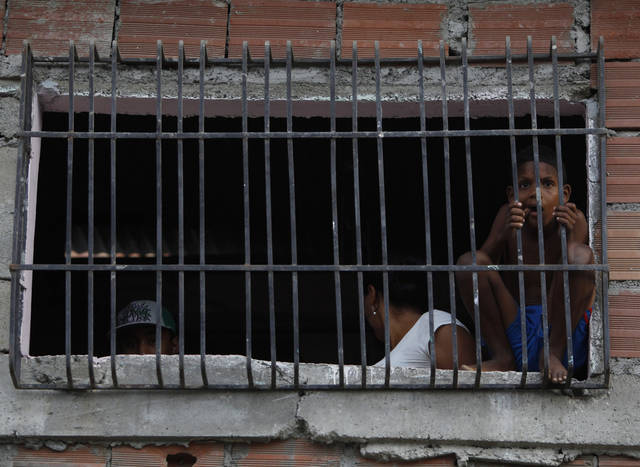 A child watches the troop activity from a window near the El Rodeo II prison in Guatire, Venezuela, Monday, June 20, 2011. Thousands of National Guard troops stormed the adjacent El Rodeo I prison complex last June 17 seeking to disarm prisoners days after a bloody riot, setting off gunfights with resisting inmates that have left at least one inmate and two soldiers dead, and more than 18 wounded. (AP Photo/Fernando Llano)