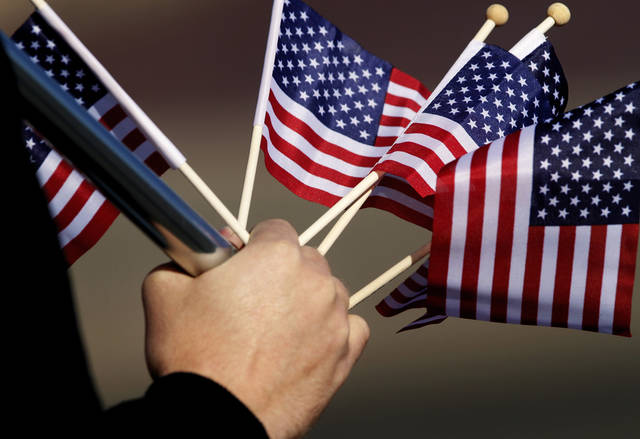 A man holds several small flags in the same hand that carries a pole bearing a larger American flag. The city of Midwest City teamed with civic leaders and local merchants to display their appreciation for veterans and active military forces by staging a hour-long Veteran's Day parade that stretched more than a mile and a half along three of the city's busiest streets Monday morning, Nov. 12, 2012. Hundreds of people lined the parade route, many of them waving small American flags that had ben distributed by volunteers who marched near the front of the parade. A fly-over performed by F-16s from the138th Fighter Wing, Oklahoma Air National Guard unit in Tulsa thrilled spectators. Five veterans representing military personnel who served in five wars and military actions served as  Grand Marshals for the parade. Leading the parade was the Naval Reserve seven-story American flag, carried by 100 volunteers from First National Bank of Midwest City, Advantage Bank and the Tinker Federal Credit Union. The flag is 50 feet by 76 feet, weighs 110 pounds and was sponsored by the MWC Chapter of Disabled American Veterans. Photo by Jim Beckel, The Oklahoman