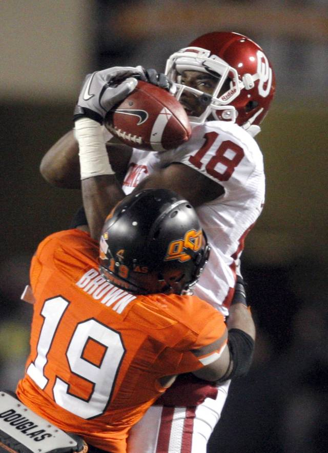Oklahoma's Kameel Jackson (18) catches the ball as Oklahoma State's Brodrick Brown (19) brings him down during the Bedlam college football game between the Oklahoma State University Cowboys (OSU) and the University of Oklahoma Sooners (OU) at Boone Pickens Stadium in Stillwater, Okla., Saturday, Dec. 3, 2011. Photo by Sarah Phipps, The Oklahoman