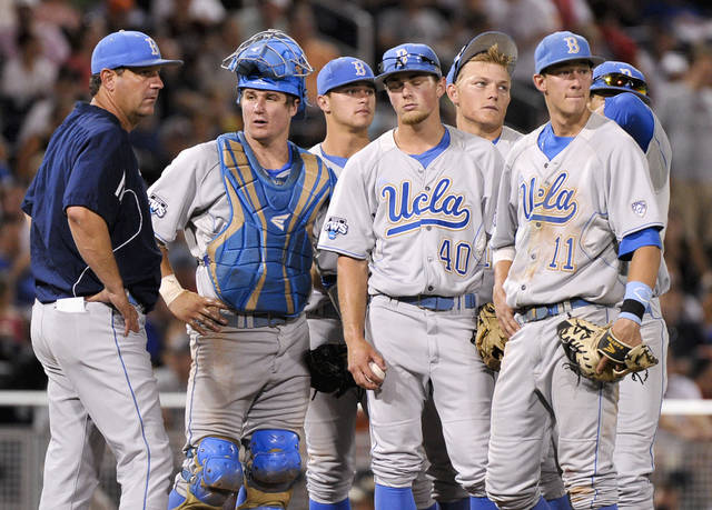UCLA coach John Savage, left, catcher Tyler Heineman, pitcher Ryan Deeter (40) and first baseman Trevor Brown (11) wait for relief pitcher David Berg to arrive at the mound, in the sixth inning of an NCAA College World Series elimination baseball game in Omaha, Neb., Tuesday, June 19, 2012. (AP Photo/Ted Kirk)