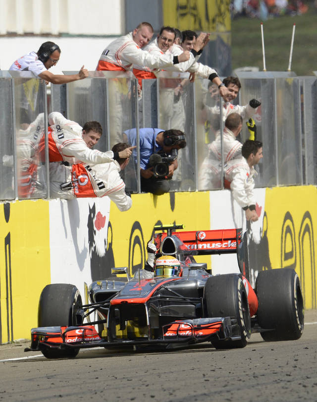 McLaren mechanics and Britain's McLaren driver Lewis Hamilton celebrate their victory at the Hungarian Formula One Grand Prix at the Hungaroring circuit outside Budapest, Hungary, Sunday, July 29, 2012. (AP Photo/Balazs Czagany)