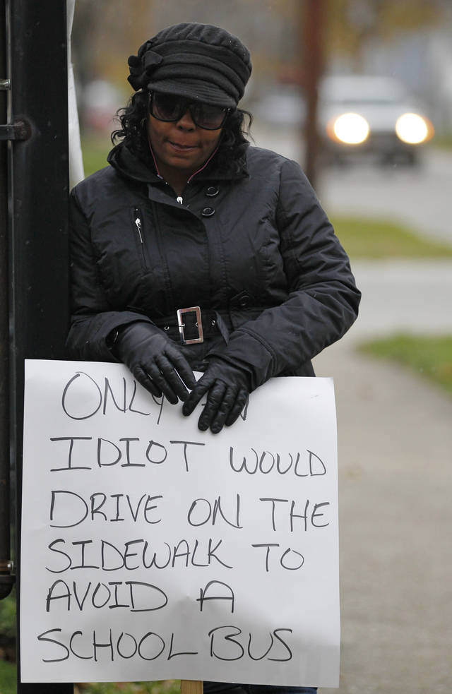 Shena Hardin holds up a sign to serve a highly public sentence Tuesday, Nov. 13, 2012, in Cleveland, for driving on a sidewalk to avoid a Cleveland school bus that was unloading children. A Cleveland Municipal Court judge ordered 32-year-old Hardin to serve the highly public sentence for one hour Tuesday and Wednesday. (AP Photo/Tony Dejak)