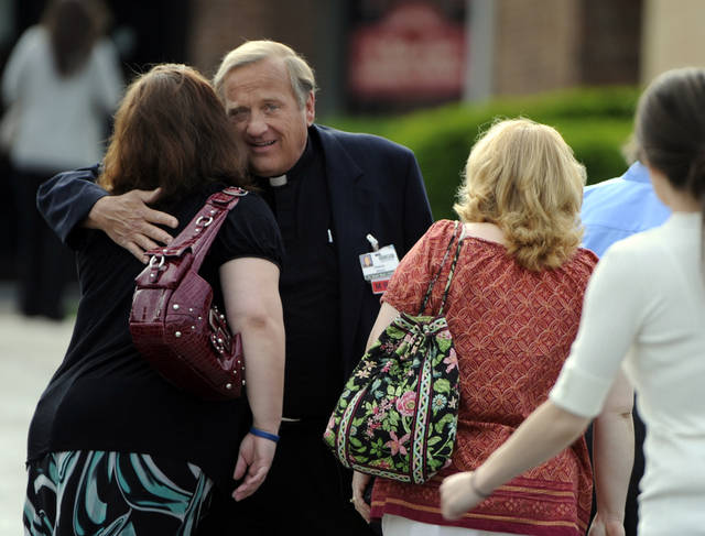 Father Francis X. Mazur of Erie County Medical Center, greets mourners before the funeral for Jacqueline Wisniewski at St. Martin of Tours Church in Buffalo, N.Y. Saturday, June 16, 2012. Wisniewski, 33, was killed Wednesday at ECMC, where she worked. Police said she was shot by ex-boyfriend Timothy Jorden, a doctor at the hospital. (AP Photo/Gary Wiepert)